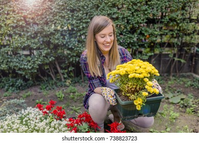 e16af8f5 Young smiling woman florist working in the garden. garden worker planting  flowers. gardening service