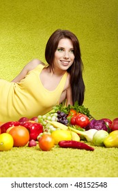 Young smiling woman with fruits and vegetables. Over green background