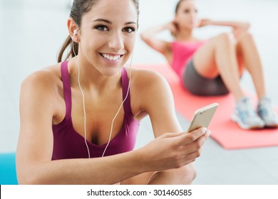 Young smiling woman at the gym having a break and listening to music using a smart phone and earphones, fitness and youth concept