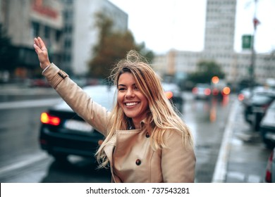 A young smiling woman hailing a cab driver in a rainy city.