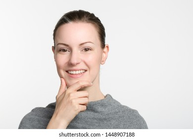 young smiling woman with hand at her chin is thinking