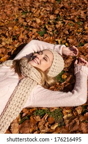 young smiling woman with hat and scarf outdoor in autumn nature background