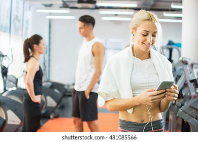 Young smiling woman having a break and listening to music using a smart phone and earphones in a gym.