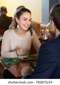 young smiling woman having dinner with a man in a restaurant