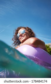 Young smiling woman having fun on pink air bed in sea water.