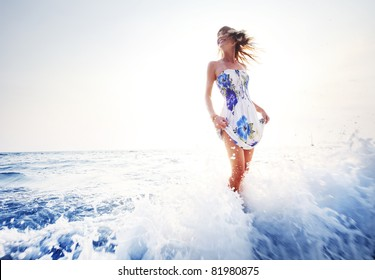 Young smiling woman having fun standing in blue sea water