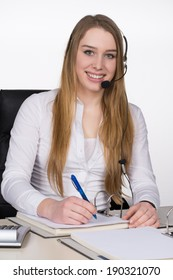 Young smiling woman with a headset sits at the desk in the office and writes into a document