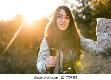 Young smiling woman hiking alone in the mountains while looking at a map at sunset