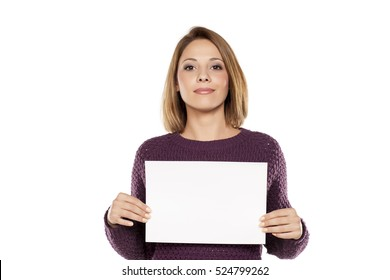 young smiling woman holding a blank sheet of paper for advertising