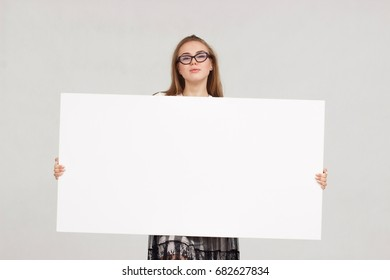 young smiling woman holding a blank sheet of paper for advertising.Girl showing banner with copy space.Smiling woman sign board holding