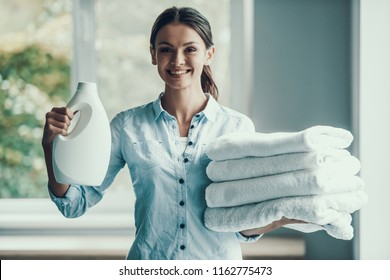 Young Smiling Woman holding Laundry Detergent. Happy Beautiful Girl holding Bottle of Loundry Detergent next to Stack of Fresh and Clean Towels. Young Attractive Woman doing Housework. House laundry