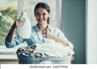 Young Smiling Woman holding Laundry Detergent. Happy Beautiful Girl holding Bottle of Loundry Detergent above Stack of Fresh and Clean Clothes. Young Attractive Woman doing Housework. House laundry