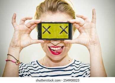 Young smiling woman holding smartphone over her eyes with two X symbols on display.