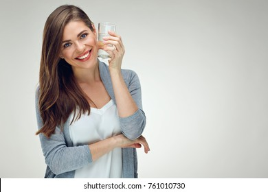 Young smiling woman holding water glass. Isolated studio portrait on white.