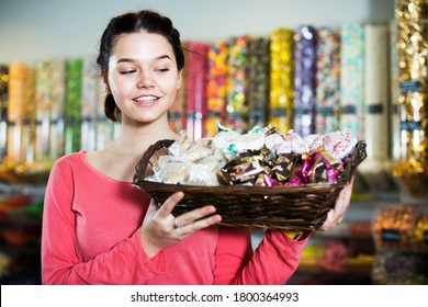 Young smiling woman holding wicker basket with chocolates and many sweets in candies shop