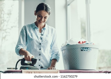 Young Smiling Woman Ironing Clothes after Laundry. Happy Beautiful Girl enjoying Ironing Clean and Fresh Clothing just after Laundry. Young Attractive Woman doing Housework. House laundry