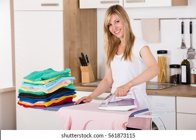 Young Smiling Woman Ironing Clothes With Electric Iron At Home