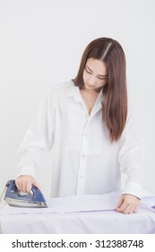 Young smiling woman is ironing a shirt with a  iron on white background.