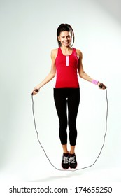 Young smiling woman jumping rope on a gray background