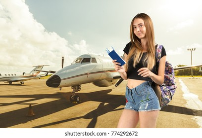Young smiling woman keeping airticket