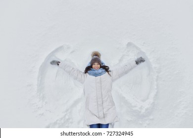 Young smiling woman kidding on snow in winter day. The girl on a snow angel shows. copyspace