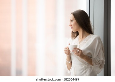 Young smiling woman in lace night gown relaxing at cozy home, feeling happy, resting in the morning, looking through the window with a cup of drink, challenge of a new day. Copy space