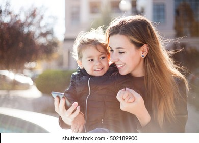 Young smiling woman and little happy girl reading message on smartphone. Autumn city background