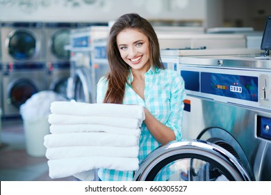 Young smiling woman looking at camera and holding a heap of white clean linen. Feeling softness of linen and freshness of washing. Girl with fresh soft washing, laundry interior
