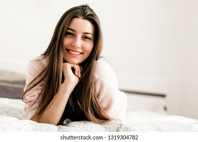 Young smiling woman lying in bed in her bedroom. Happy morning.