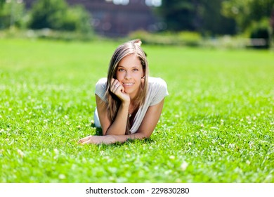 Young smiling woman lying down on the grass
