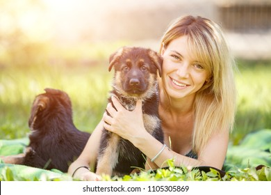 Young smiling woman lying on grass with small puppy of german shepherd