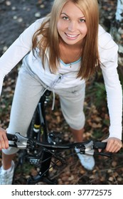 Young smiling woman on the bicycle in the autumn forest