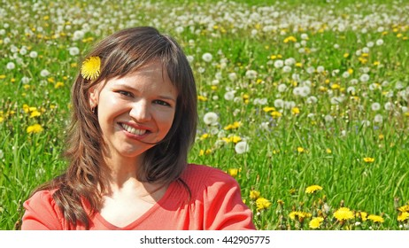 Young smiling woman on dandelion field.