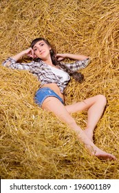 Young smiling woman on haystack
