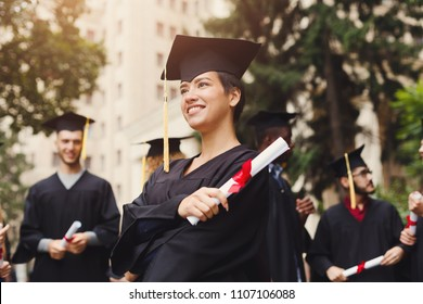 Young smiling woman on her graduation day in university, standing with multiethnic group of students. Education, qualification and gown concept.