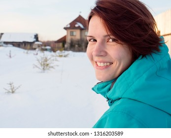 Young smiling woman on the nature in the village in winter