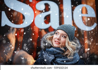 Young smiling woman on shop window background. Winter sales concept