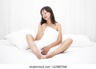 Young smiling woman on white sofa in hotel room.