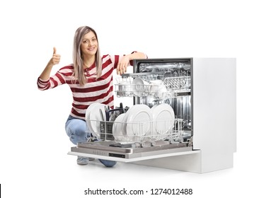 Young smiling woman with an open full dishwasher giving thumbs up isolated on white background