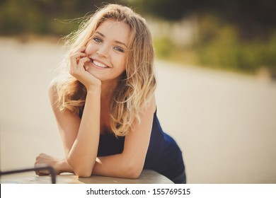 Young smiling woman outdoors portrait. Soft sunny colors.Close portrait.