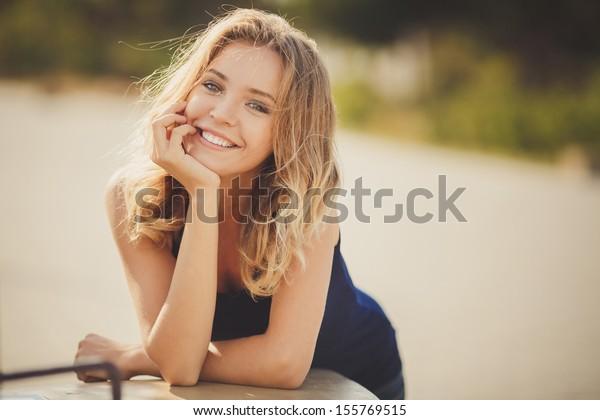 屋外で若い笑顔の女性のポートレート。晴れやかな色。ポートレートを閉じる。