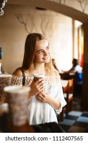 Young smiling woman with paper cup in cafe talking to someone. Young people meeting in a cafe.