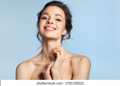 Young smiling woman with perfect face and hand beauty studio portrait on blue copyspace. Beautiful brunette spa girl with glowing hydrated facial skin touching healthy palm. Skincare and cosmetology