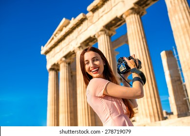 Young and smiling woman photographer taking picture with professional camera of Parthenon temple in Acropolis