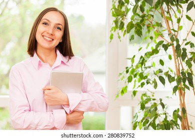 Young smiling woman with a pink shirt standing with a tablet pc in her hands