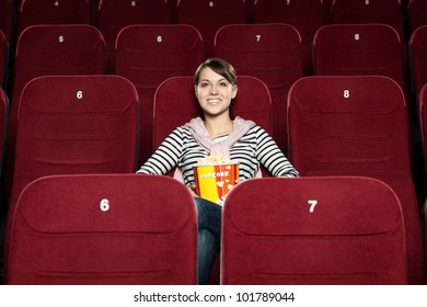 Young smiling  woman with popcorn at the cinema