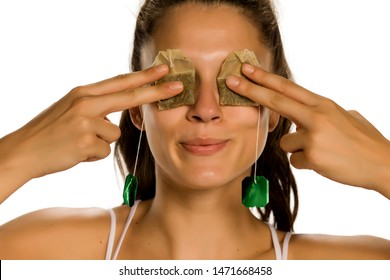 Young smiling woman posing with tea bags on her eyes on white background