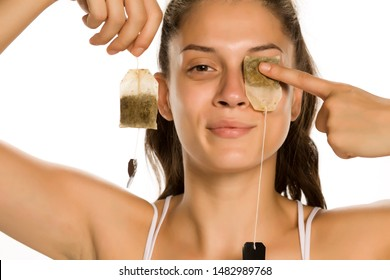 Young smiling woman posing with tea bag on her eye on white background