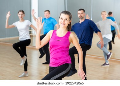 Young smiling woman practicing vigorous lindy hop movements in dance class