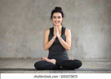 Young smiling woman practicing yoga, doing Padmasana exercise, Lotus pose, working out, wearing sportswear, black pants and top, indoor full length, yoga studio window, looking at the camera